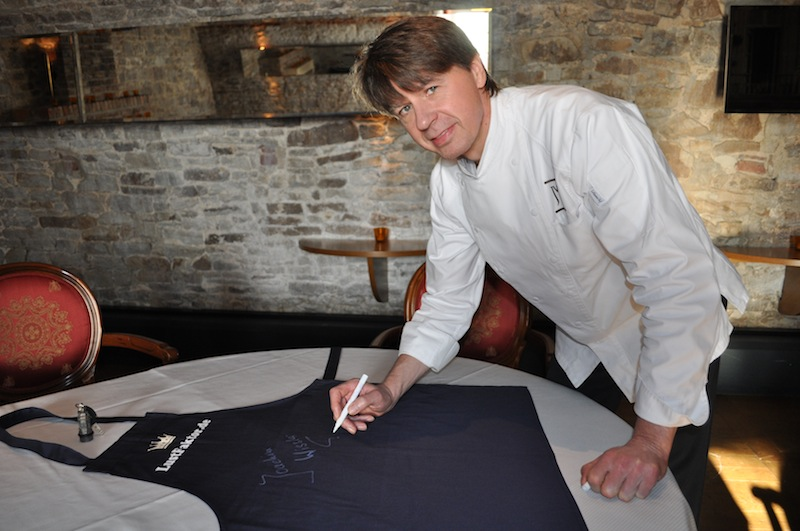 Joachim Wissler unterschreibt als erster 3-Sterne-Koch auf der FrontRowSociety.net Schürze / © Redaktion FrontRowSociety.net