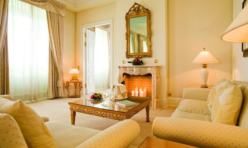 Die großzügige Sofa-Ecke vor dem offenen Kamin lädt in der Präsidenten Suite zum Verweilen ein / © Althoff Grandhotel Schloss Bensberg