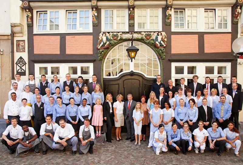 Das Team und die Eigentümer vor dem Eingang zum Restaurant Walhalla / © Romantik Hotel Walhalla