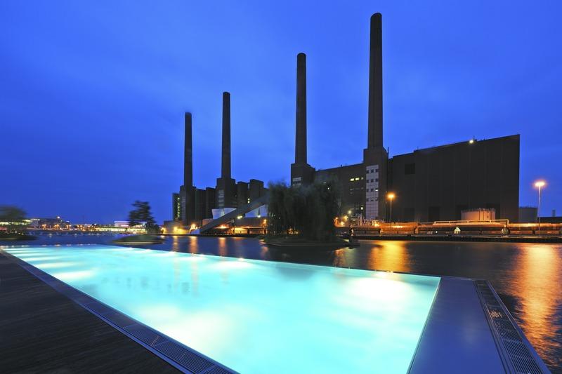 Hier ein abendlicher Blick über den 40 Meter langen Pool zum unter Denkmalschutz stehenden Volkswagen Kraftwerk / © The Ritz-Carlton, Wolfsburg