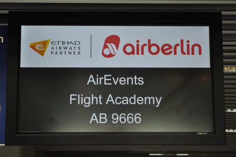 """Die anderen Flugpassagiere machen verduzte Gesichter, wenn sie auf die Anzeigetafel schauen. Eigentlich sollte hier angezeigt werden, wo es hingeht. Gleiche, verdutzte Gesichter durften wir auch schon bei den airberlin Sonderflügen """"Polarlichtjagd"""" und """"Flug zum Nordpol"""" sehen / © Redaktion FrontRowSociety.net"""