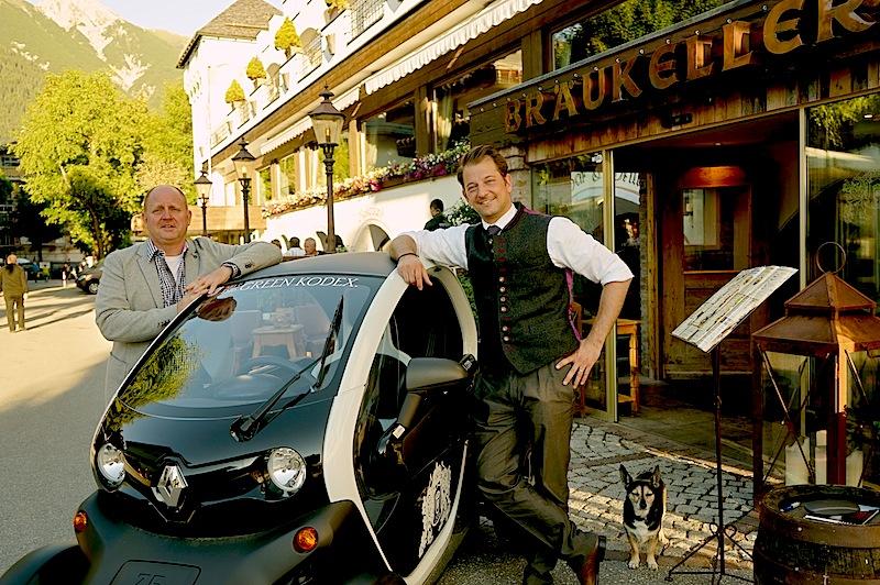 Herausgeber Andreas Conrad (l.) und Hotelchef Alois Seyrling mit dem E-Mobil Renault Twizy / © Redaktion FrontRowSociety.net, Foto Martin Scheidtmann
