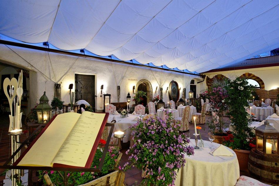 Am Abend ist es ein einmaliges Erlebnis im Klosterhof zu dinieren. Ein luftiger Baldachin schützt die speisenden Gäste / © Hotel Klosterbräu