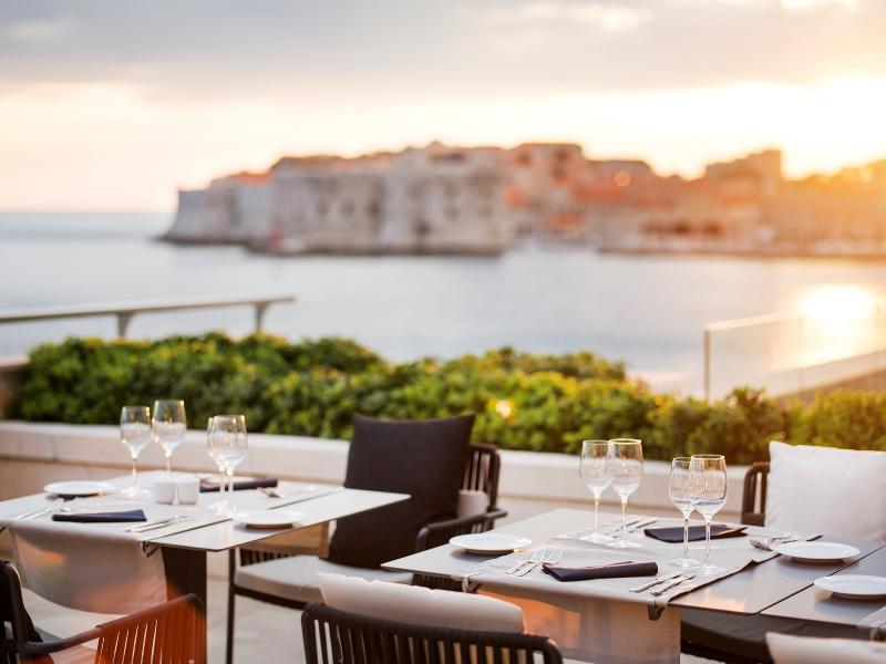 Die Abakus Terrasse ins Licht der untergehenden Sonne getaucht. Im Hintergrund ist die Altstadt von Dubrovnik zu sehen / © Adriatic Luxury Hotels