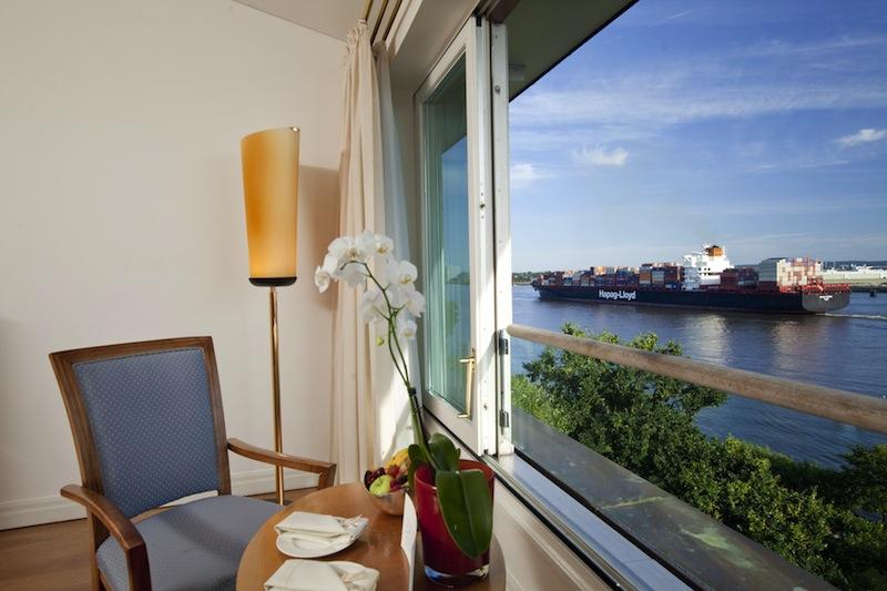 Auf dem Tisch vor dem großen Panoramafenster liegt ein Fernglas; so entgeht keinem Gast das Treiben auf der Elbe / © Louis C. Jacob