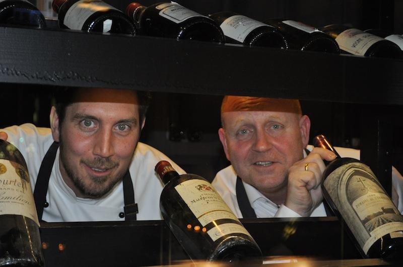 Mit Sternekoch Michael Kammermeier (l.) ist Andreas Conrad, Herausgeber vom Luxus & Lifestyle Magazin FrontRowSociety.net gerne auf der Suche nach einer guten Flasche Rotwein / © Redaktion FrontRowSociety.net