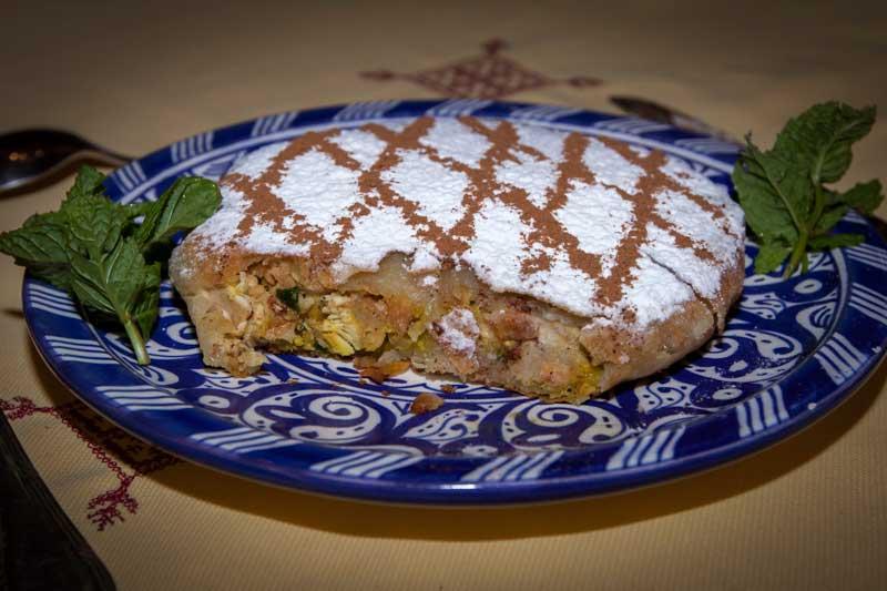 Eine in Marokko Pastilla genannte Blätterteigpastete bildet die Vorspeise. Bei einer angenehm milden Zimtanmutung verträgt sich das Hühnerfleisch erstaunlich gut mit den untergehobenen Eiern, mit Petersilie, Zwiebeln, Mandeln und Ingwer / © FrontRowSociety.net, Foto Georg Berg