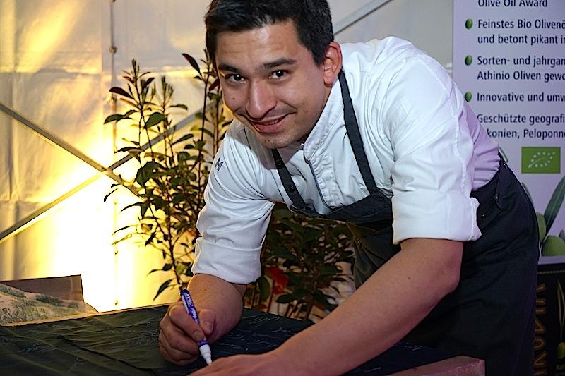 2-Sterne-Koch Tohru Nakamura bei der Unterschrift auf die FrontRowSociety.net-Schürze, welche - zusammen mit einer großen Auswahl an Weinen - für einen guten Zweck versteigert wird