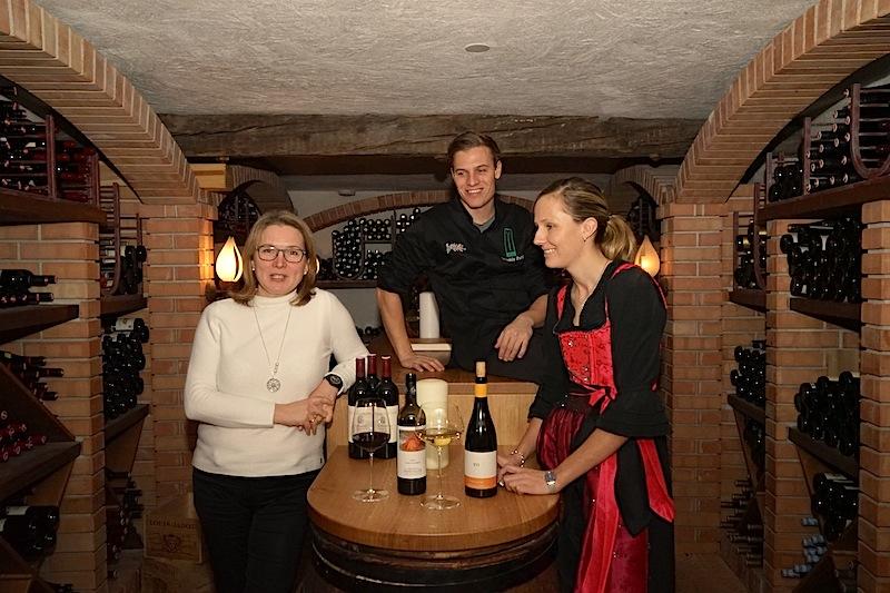 Sarah obliegt die Restaurantleitung im Stüva, außerdem ist sie als Master Sommelier Herrin über den ansehnlichen Weinkeller des Genießerhotels Yscla. Hier im Weinkeller v.l.n.r.: Redakteurin Annett Conrad, Benjamin Parth und Sarah Falch