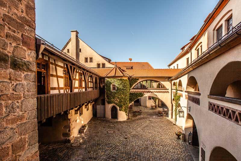 Ein Burghof – wie es sich gehört – mit Türmchen, Bögen und verborgenen Winkeln