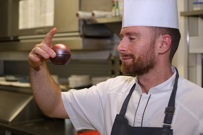 Endkontrolle: Küchenchef Daniel Groß überprüft mit kritischem Blick, ob seine Schokoladenkugel den Giant-Kugeln vom Aasee ähnelt