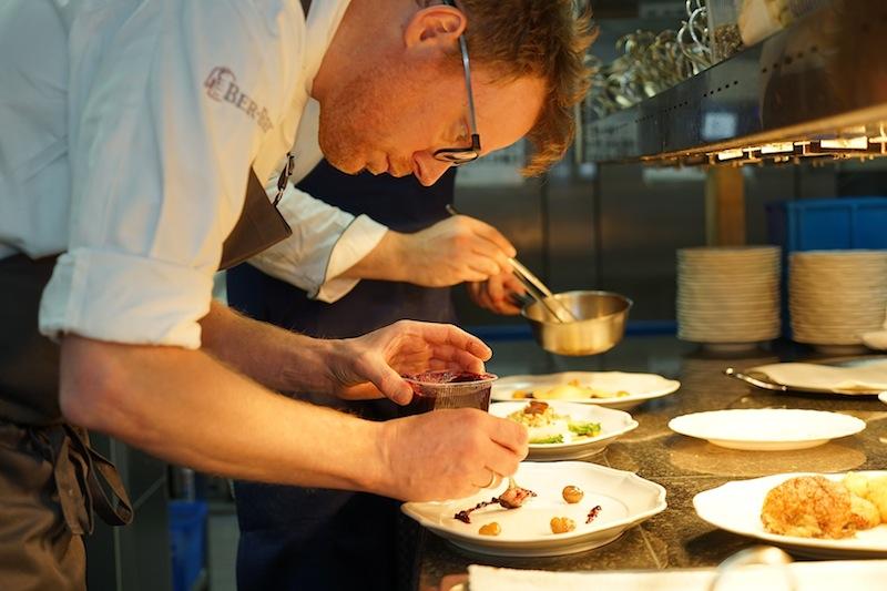 Oliver Windau konzentiet über die Teller gebeugt. Tüpfelchen für Tüpfelchen muss passen; optisch und auch im Geschmack