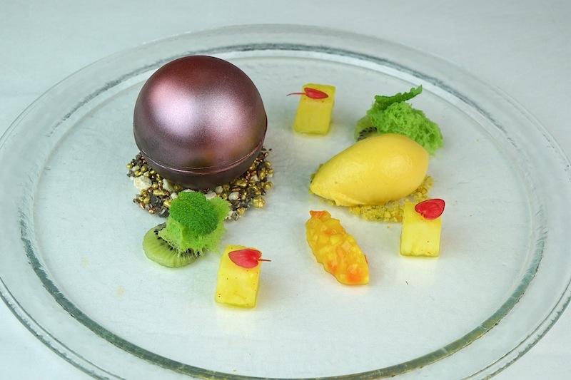 Die Kugel auf dem Dessertteller musste zuerst zerbrochen werden, um den Kern aus Schokoladenganache zu erreichen