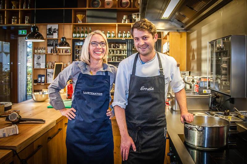 Koch Felix Groß in der offenen Küche des Ernerle mit FrontRowSociety.net Redakteurin Angela Berg. Im Hintergrund Regale voll mit regionalen Spezialitäten