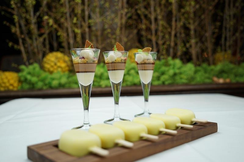 Hübsch aufgereiht: Pousse Café mit Röstbanane und Blue Mountain und einem Eis am Stiel aus weißer Schokolade und Curry