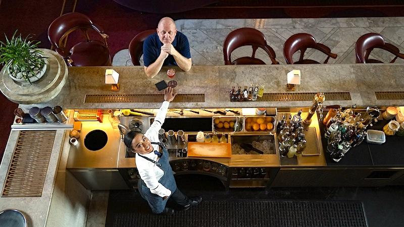 Herausgeber des Luxus & Lifestyle Magazins FrontRowSociety.net, Andreas Conrad, in der ATLAS Bar in Singapur. Bartender Yana Binte Kamaruddin kredenzt gerade den bekannten Café Royale Spezial