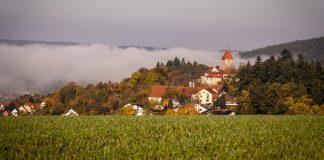 Die grüne Hügellandschaft der Oberpfalz und mitten drin im Morgennebel Burg Wernberg