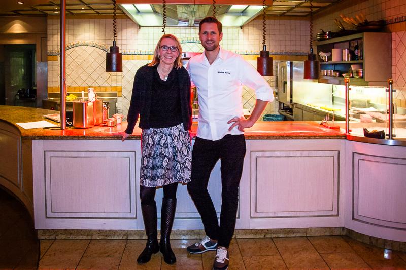 Michael Kempf zusamen mit Front-Row-Society Autorin Angela Berg vor der offenen Küche im Parkhotel Ahrensburg / © FrontRowSociety.net, Foto Georg Berg