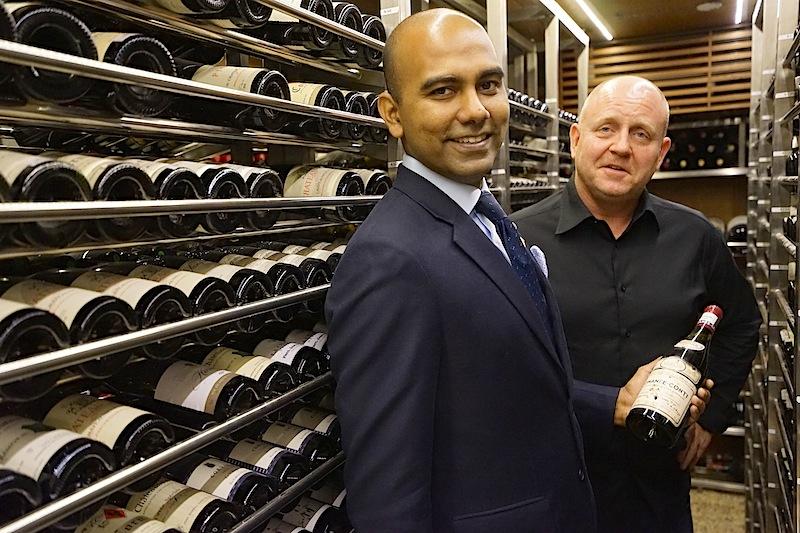 Chef Sommelier Rajeshwaran Raja Gopal (li.) ist stolz auf seinen exzellenten Bestand an ausgesuchten Weinen. Hier mit einem 1978er Ausnahmewein von Romanée-Conti