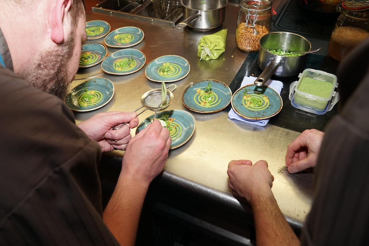 Viele fleißige Hände richteten Jacobsmuschel mit Erbse, Ziegenquark, Zitrone und Estragon her