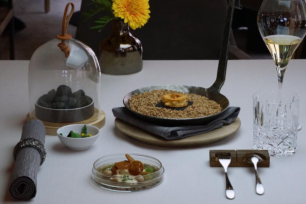 Auftakt mit alpenlandischen Klassikern: In der rustikalen Pfanne findet sich ein Kasspatzen, dessen dazugehöriger Kopfsalat wartet farbenfroh im weißen Schälchen. Die noch dampfenden Erdäpfel in Heuasche, Leinöl und Kräutern verstecken sich unter der Glasglosche während sich Speckknödel, Sauerkraut und Traube auf dem Teller aus Glas präsentieren