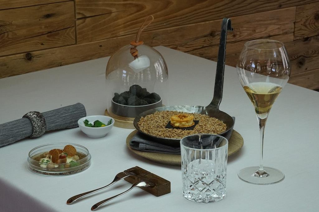 Start mit alpenländischen Klassikern: In der Pfanne finden sich Speckknödel mit Sauerkaut und Traube, verborgen unter der Glasglosche noch dampfende Erdäpfel in Heuasche, Leinöl und Kräutern und auf dem Teller aus Glas präsentieren sich Kasspatzen auf Kopfsalat