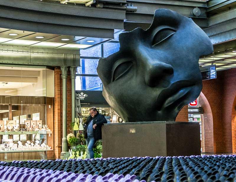 Eine monumentale Maske des polnischen Bildhauers Igor Mitoraj steht mitten in der Shopping Mall der Stary Browar – ein weiteres Beispiel für die Verbindung von Kunst und Gewerbe / © FrontRowSociety.net, Foto Georg Berg