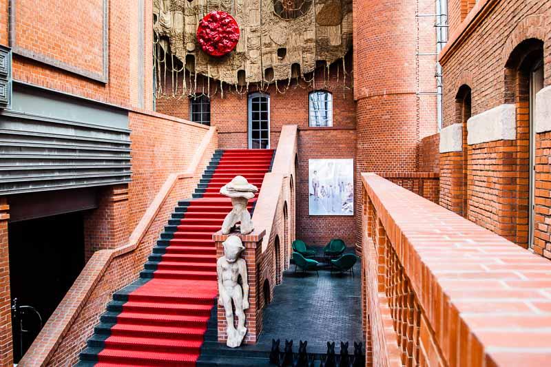 In der Eingangshalle des Hotels finden sich den Raummaßen entsprechend auch die größten Kunstwerke. Darunter der Wandteppich von Piotr Uklański über dem Eingang der Bar und Holzskulpturen von Sylwester Ambroziak am Treppenaufgang / © FrontRowSociety.net, Foto Georg Berg