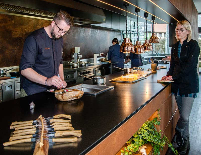 Das Team von Heiko Lacher ist im wahrsten Sinne überschaubar, denn der Sternekoch und seine beiden Köche hantieren hinter einer langen offenen Küche, die den ganzen Gastraum flankiert / © FrontRowSociety.net, Foto: Georg Berg