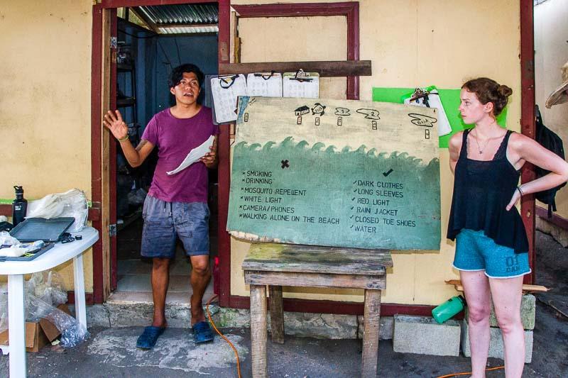 Die Regeln am Strand sind verbindlich und passen auf eine Tafel. Scientist Fabian Carrosco und Research Assistant Grace Kibblewhite beim Einführungsvortrag / © FrontRowSociety.net, Foto: Georg Berg
