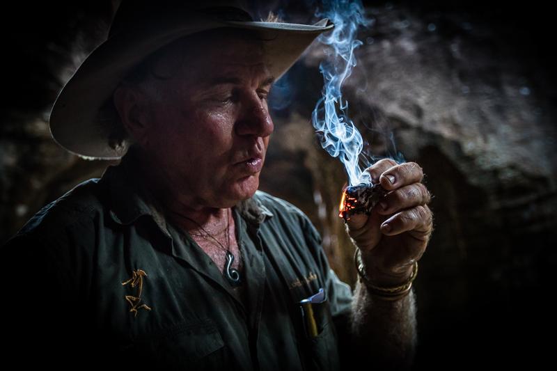 """Sab Lord zündet ein von Termiten bearbeitetes Stück Holz an, um mit dem Rauch die Mücken zu vertreiben. Ein altes """"Hausmittel"""" der Aborigines / © FrontRowSociety.net, Foto: Georg Berg"""
