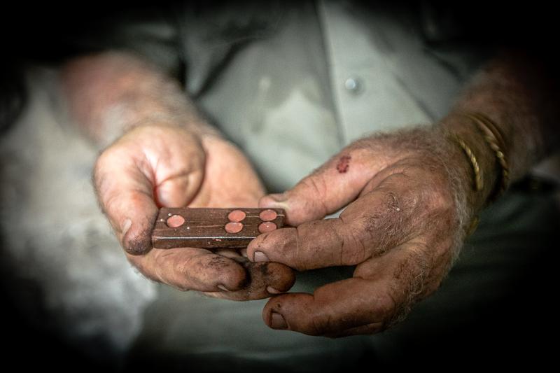 Sab Lord hält einen Dominostein in der Hand, der in einer Aborigine-Höhle hinterlegt worden ist / © FrontRowSociety.net, Foto: Georg Berg