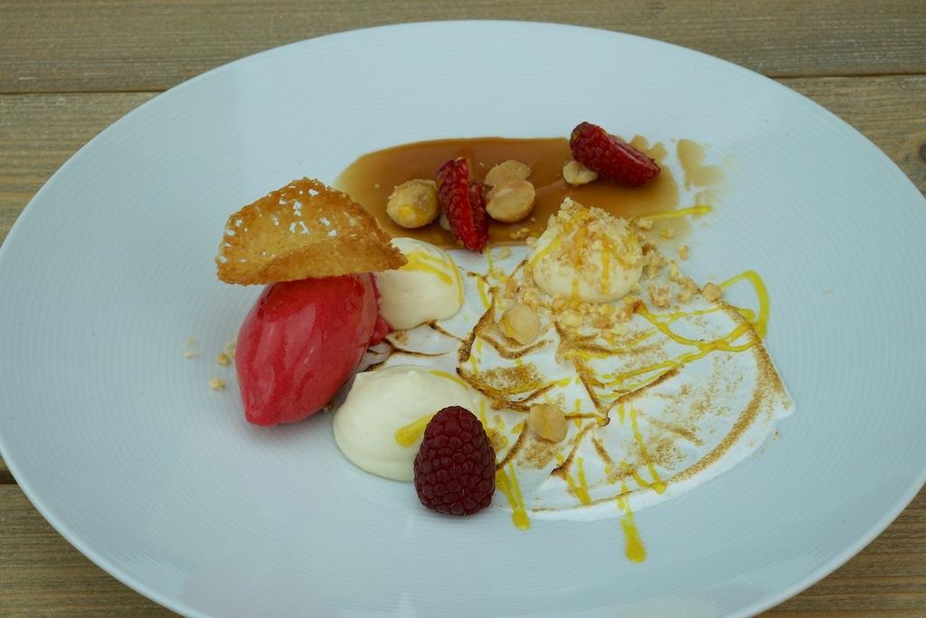 Ein leichtes Dessert aus Yuzu Milch Tart mit Karamell, Macadamianüssen und Mandeln, getrockneter Kokosnuss, einem Sorbet von Himbeere und Thymian sowie Meringue