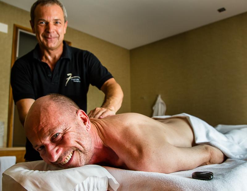FrontRowSociety Chefreporter Georg Berg freut sich über eine entspannende Massage, bei der auch heiße Kieselsteine aus dem Flussbett der Simme zum Einsatz kommen / © FrontRowSociety.net, Foto: Moritz Berg