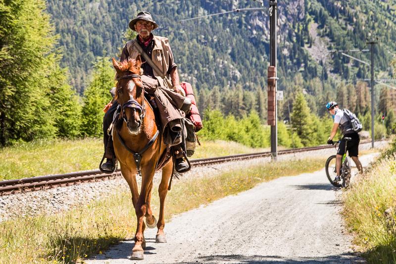 Da staunt der Hoteldirektor auf dem E-Bike. Einen Reisenden, der hoch zu Ross Graubünden durchquert, sieht auch er nicht alle Tage / © FrontRowSociety.net, Foto: Georg Berg