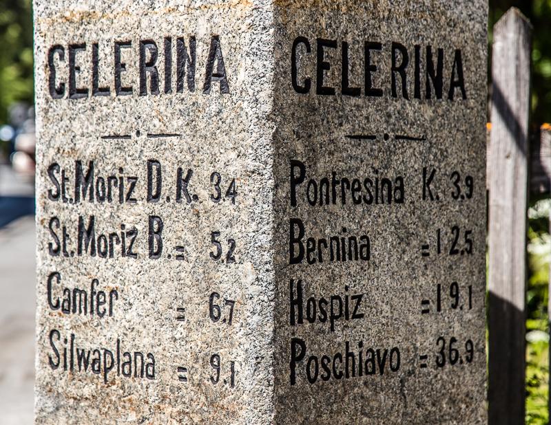 Mitten in Celerina weist ein Markierungsstein auf die Nachbarorte hin / © FrontRowSociety.net, Foto: Georg Berg