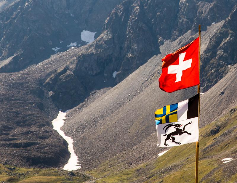 Die Fahne des Kantons Graubünden besteht aus drei Teilen und erinnert damit an die drei Bünde, aus denen der heutige Kanton hervorging. Der schwarze Steinbock als Emblem des Gotteshausbundes, das geteilte Feld für den grauen Bund und das Blau-gelbe Kreuz für den Zehngerichtebund / © FrontRowSociety.net, Foto: Georg Berg