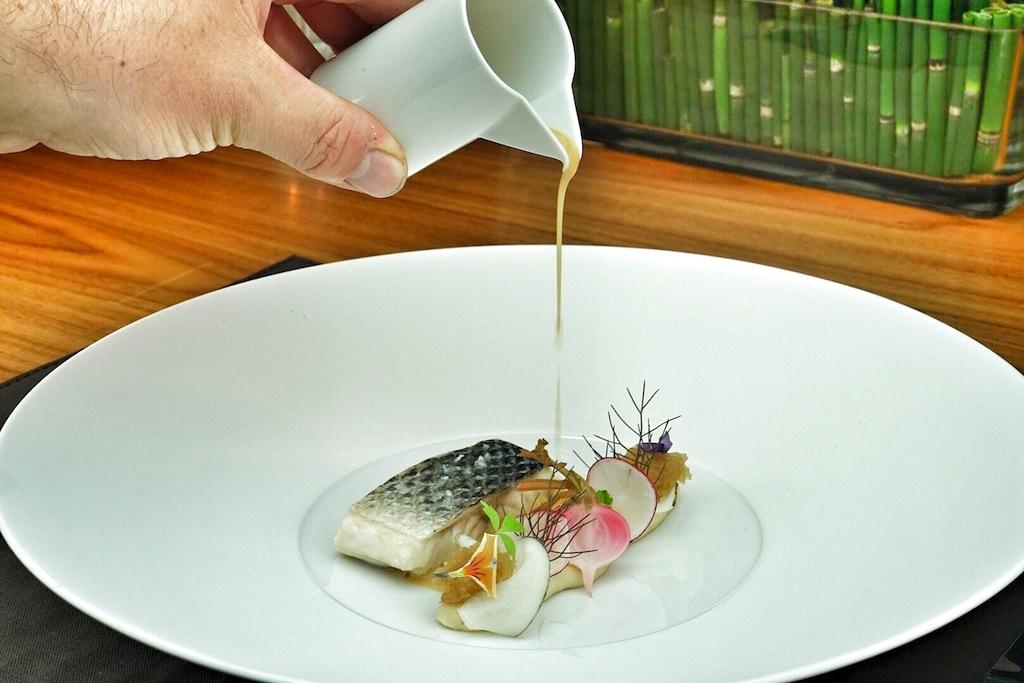 Wer die Nähe zu den Akteuren der Küche mag, sitzt am Chefs Table genau richtig, auch der Fond für Loup de Mer, weiße Bohne und Rettich wird vom Chefkoch persönlich angegossen