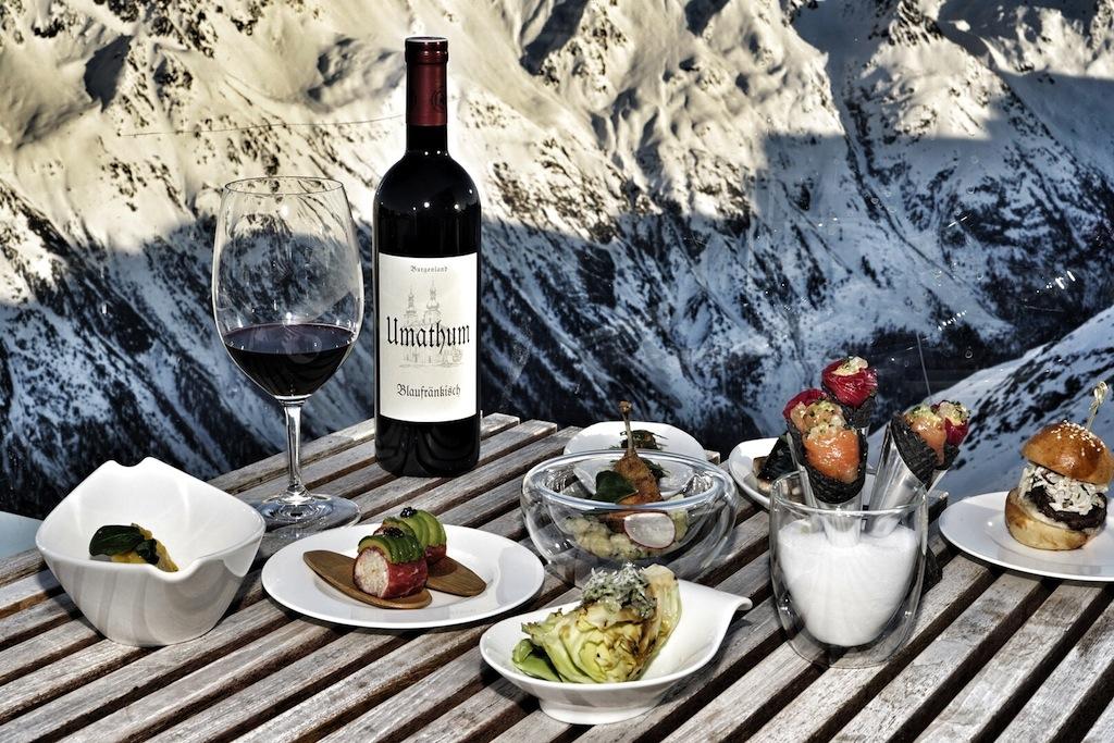 """Im Licht der untergehenden Sonne über der Ötztaler Bergwelt gab es auf der Skihütte 2.0 """"ice Q"""" leckeres Fingerfood mit erstklassigen Wein zu genießen, hier mit dem Blaufränkisch vom Weingut Umathum"""