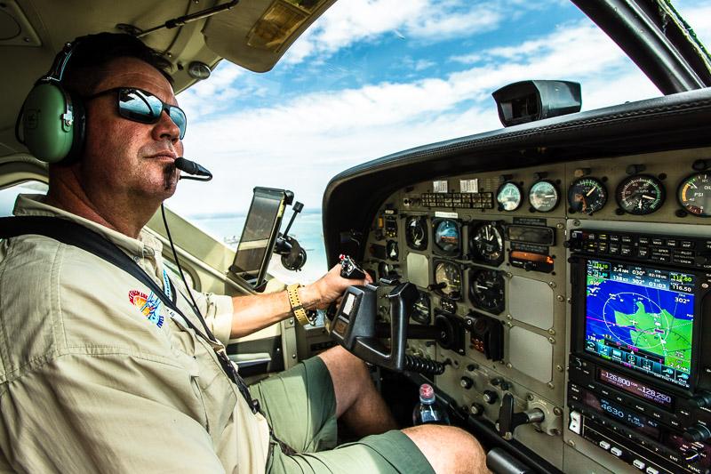 Pilot Dave am Steuerknüppel seines Flugzeugs, mit dem er sowohl auf festen Rollfeldern als auch auf Füssen und Seen starten und landen kann / © FrontRowSociety.net, Foto: Georg Berg