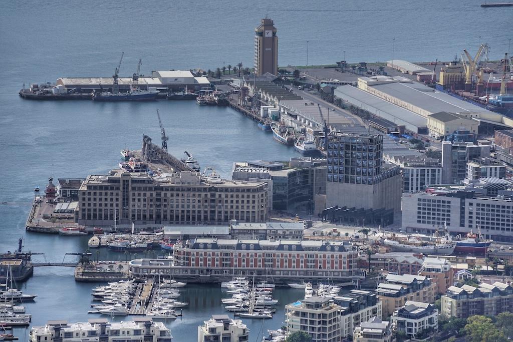 Aus der Vogelperspektive kann man gut die Umrisse des Kreuzfahrtschiffs erkennen. Zur einen Seite liegt der ruhige Yachthafen und zu anderen der quierliege Arbeiterhafe