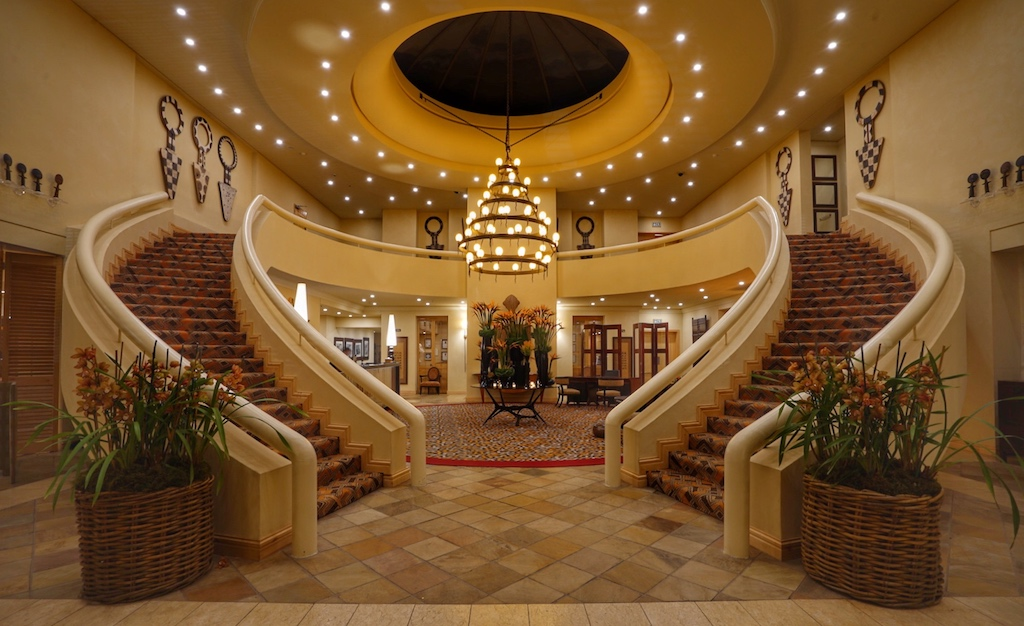 Nach dem Durchschreiten der hohen Eingangstür erwarten den Gast eine großzügige Lobby mit zwei geschwungenen Treppenaufläufen