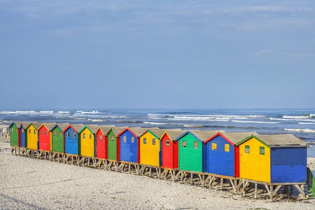 Die bunten Badehäuschen sind das Markenzeichen von Muizenberg und ganzjährig zu mieten. Die False Bay bietet perfekte Bedingungen für Surfer. Obwohl sich auch Haie in diesen Gewässern tummeln, erfreut sich der Badeort doch wieder wachsender Beliebtheit