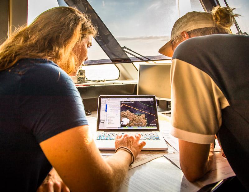 Angela und Jeremy planen auf der Brücke der True North anhand von Seekarten und Onlineinformationen die Tauchgänge des nächsten Tages / © FrontRowSociety.net, Foto: Georg Berg