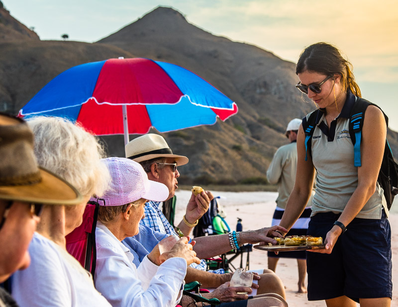Picknik am rosa Strand von Pulau Padar. Zu den Beach-Drinks gibt es für die Gäste Meredith-Ziegenkäse-Törtchen mit karamelisierten Zwiebeln/ © FrontRowSociety.net, Foto: Georg Berg