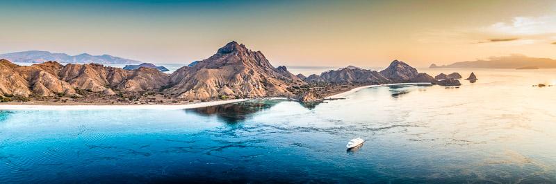 Die True North liegt bei Gili Lawadarad vor Anker, während die Gäste am Strand auf den Sonnenuntergang warten. Die Inselgruppe der kleinen Sundainseln ist Teil des Pazifischen Feuerrings / © True North, Foto: Oliver Oldroyd