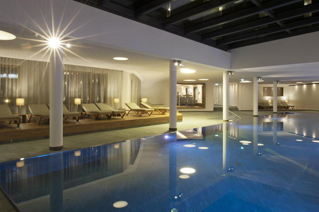 Im Kitzbühel Country Club entspannen die Mitglieder im Pool aus Naturstein