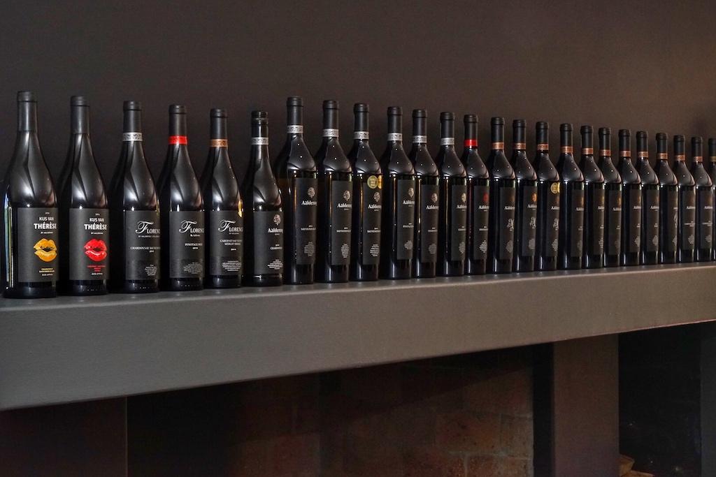 Über dem Kamin des Verkostungsraums reihen sich viele leere Flaschen der letzten Jahrgänge auf