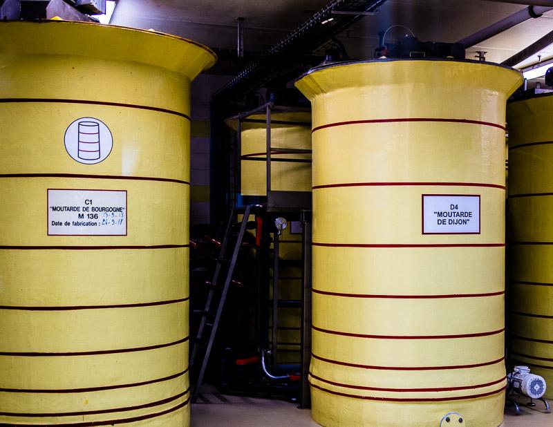 Eintraechtig nebeneinander stehen die Lagerbehaelter für Dijon-Senf und Burgund-Senf. 24 Stunden ruht der fertige Senf hier, bevor er abgefuellt wird / © FrontRowSociety.net, Foto: Georg Berg