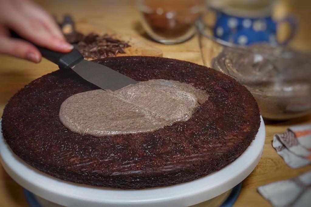 Die Oreo-Buttercreme wird den ausgekühlten und geteilten Tortenboden gestrichen - ein fest für Schokoliebhaber